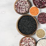 Various beans in bowls. Set of various beans in bowls: white, black, purple and red speckled beans, red and green lentils. White wooden background, top view Royalty Free Stock Images