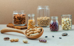 Various beans and nuts in the glass on brown background. mung be