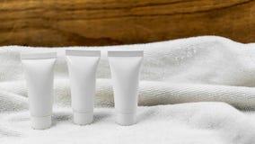 Various beauty hygiene tubes on towel Stock Photos