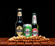 Various beer bottles. ZAGREB , CROATIA - JANUARY 24 ,2014 :  Beer bottles on black background, Beck's , Guinness , Heineken with peanuts and huzelnuts on the Stock Image