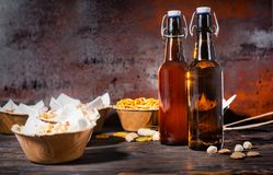Various beer snacks in plates like pistachios, small pretzels an. D peanuts near two beer bottles on dark wooden desk. Food and beverages concept royalty free stock photography