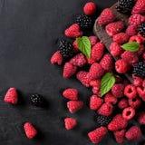 Various berries on a black background. Raspberries, blackberries. top view Royalty Free Stock Photo