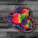 Various berries in a bowl in the form of heart Stock Images
