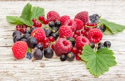 Various berries on an old wooden plank close-up Stock Photos