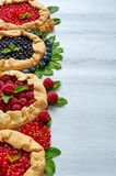 Various berries tarts on the gray concrete background. Vegetarian healthy galette decorated with fresh blueberries, raspberries royalty free stock photography