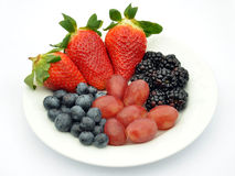 Various berries on white plate Royalty Free Stock Photo