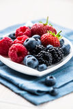 Various berry fruits on a plate Stock Photos