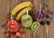 Various berry smoothies. On a brown background stock photography