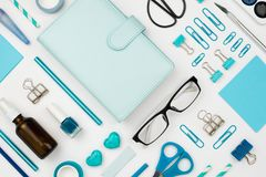 Various blue stationary and office tools and accessories knolled together. On white: planner, pens, pencils, clips, glasses, scissors, etc. Flatlay Royalty Free Stock Images