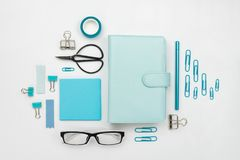 Various blue stationary and office tools and accessories knolled together. On white: planner, pens, clips, glasses, scissors, etc. Flatlay Royalty Free Stock Photos