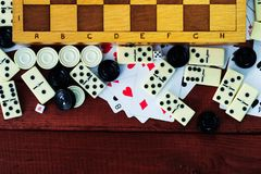 Various board games chess board, playing cards, dominoes. Royalty Free Stock Images