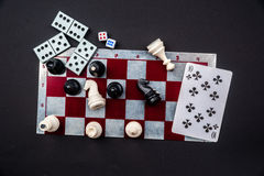Various board games. And figurines over checkers board and dark background. Metaphor for gaming and gambling Royalty Free Stock Photography