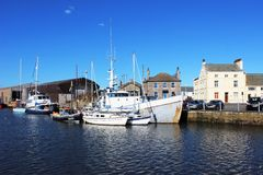 Various boats in Glasson Dock basin, Lancashire. View of several different types and sizes of boats moored in the lower basin at Glasson Dock near Lancaster Royalty Free Stock Image