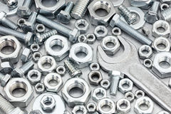Various bolts and screws of different size with wrench on scratc Stock Photography