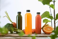 Various bottle of juice on a wooden table in the garden stock images