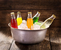 Various bottles of soda in the bucket with ice Stock Photography