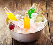 Various bottles of soda in the bucket with ice Stock Photos