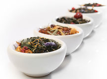 Various bowls of premium tea leaves. Blends, over white royalty free stock images