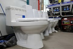 Various brands of new toilet bowl stock image