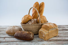Various bread loaves on wooden surface. Against white background stock photo