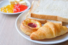 Various breads and Croissants with Jams on breakfast table. Stock Photography