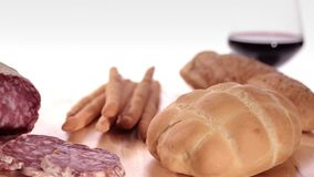 Various breads. Sliced saucisson with wine and bread in front of white background stock video
