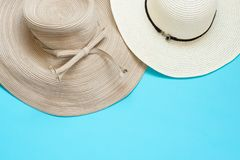 Various broad brimmed women`s straw hats on light mint blue background. Summer vacation fashion accessories beach. Party concept. Top view flat lay. Minimalist royalty free stock photo