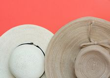 Various broad brimmed women`s straw hats on trendy coral pink background. Summer vacation fashion accessories beach party. Concept. Top view flat lay royalty free stock image