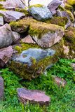 Boulders close up, stacked. Various brown and mottled boulders close up, stacked, some of them overgrown with moss and grass stock images