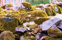 Various brown and mottled boulders close up. Stacked, some of them overgrown with moss and grass royalty free stock images