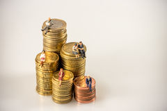 Various businesspeople sitting on money coin piles. royalty free stock photo
