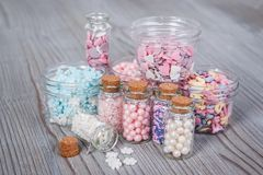 Various candy sprinkles in tiny storage cases. On wooden board Stock Photos