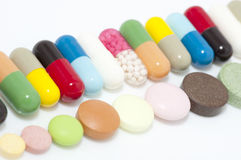 Various capsules and tablets in row stock photography
