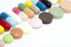 Various capsules and tablets in row stock photos