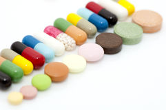 Various capsules and tablets in row stock photo