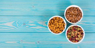 Various cat food. Dry and wet cat food. Copy space. Bowls with cat food on wooden background stock photography