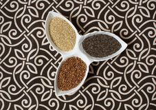 Various cereals, cereals. Different kinds of grits in bowls on a patterned, black and white background. Buckwheat grain, chia, che royalty free stock image