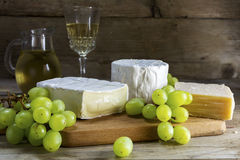 Various cheese with grapes and wine on dark rustic wood Royalty Free Stock Photography