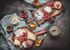 Various cheese served on rustic cutting boards with grape and wine, dark vintage background. Top view Stock Images