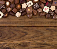 Various chocolates on wooden background Stock Photo