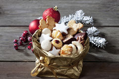 Various Christmas cookies in golden sacket on wooden background Stock Photo