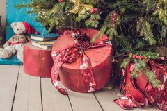 Various Christmas presents under the illuminated Christmas tree.  Stock Photo