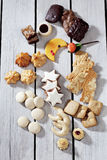 Various christmas sweets, moon shaped cookie, cinnamon stars, macaroon, spritz cookie, gingerbread on wooden background Royalty Free Stock Image