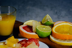 Various citrus fruit cut into slices orange, lemon, lime, grapef. Ruit, pomelo and a glass of orange juice. Spread out on a wooden board and a vintage white Royalty Free Stock Photos