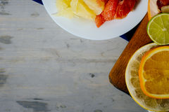 Various citrus fruit cut into slices orange, lemon, lime, grapef. Ruit, pomelo and a glass of orange juice. Spread out on a wooden board and a vintage white Stock Photos