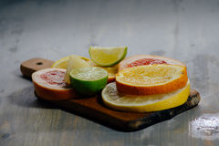 Various citrus fruit cut into slices orange, lemon, lime, grapef. Ruit, pomelo. Spread out on a wooden board on a vintage background of natural wood texturing Royalty Free Stock Images