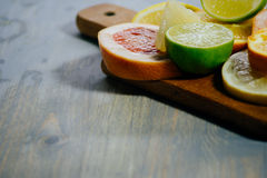Various citrus fruit cut into slices orange, lemon, lime, grapef. Ruit, pomelo. Spread out on a wooden board on a vintage background of natural wood texturing Royalty Free Stock Photography