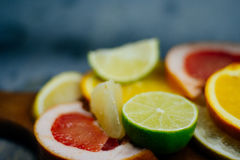 Various citrus fruit cut into slices orange, lemon, lime, grapef. Ruit, pomelo. Spread out on a wooden board on a vintage background of natural wood texturing Royalty Free Stock Photos