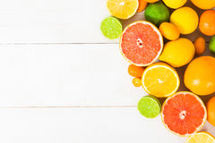 Various citrus fruit on the white wooden table. Various citrus fruit orange, lemon, lime, grapefruit, kumquat on the white wooden table with copy space Royalty Free Stock Photos