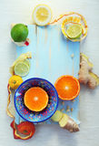 Various citrus fruits and ginger on blue cutting board Royalty Free Stock Images